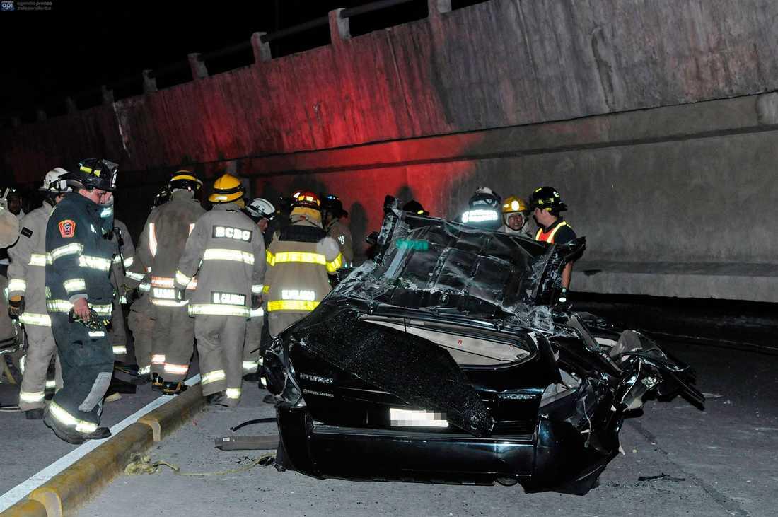 Räddningsarbetare vid en förstörd bil efter att en bro kollapsat under jordbävningen.