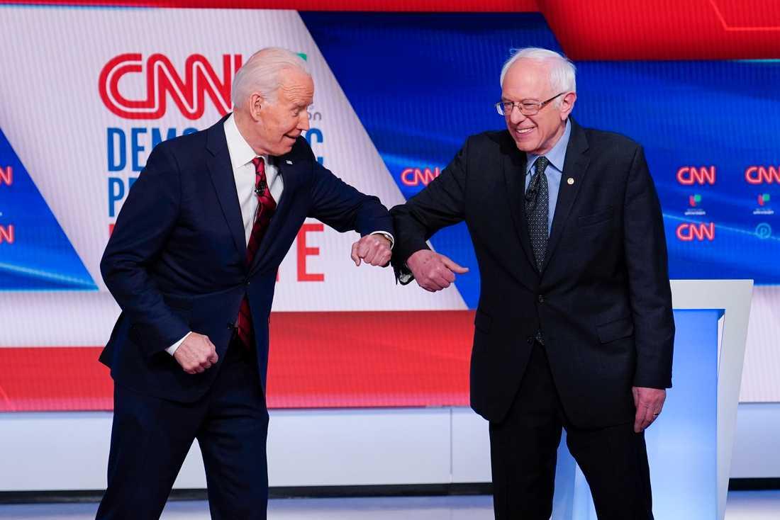"""Den tidigare vicepresidenten Joe Biden och Vermontsenatorn Bernie Sanders, båda demokrater, gör en """"virushälsning"""" före en tv-debatt i mars."""