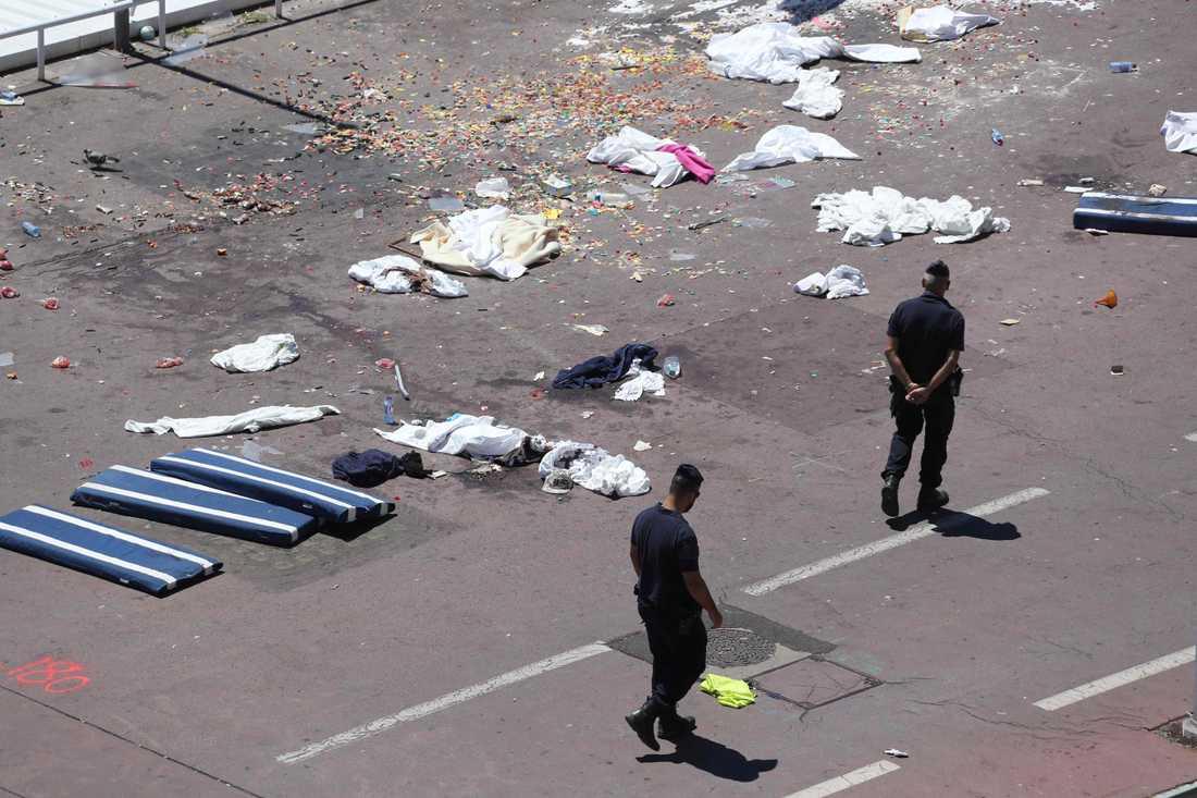 Polismän går på fredagen förbi kläder och madrasser vid platsen för terrorattacken.