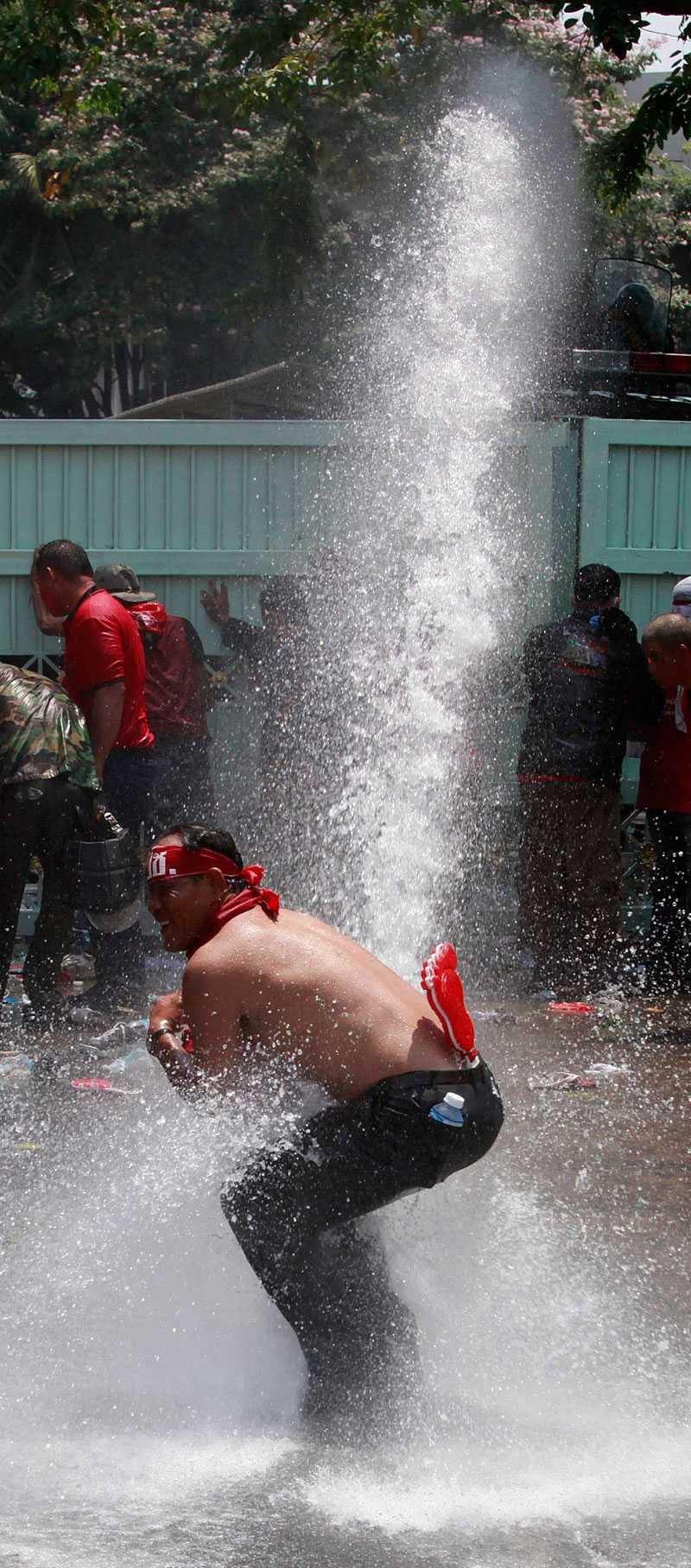 träffad av kanonen En av rödskjortorna hamnade mitt i skottlinjen för polisens vattenkanon.