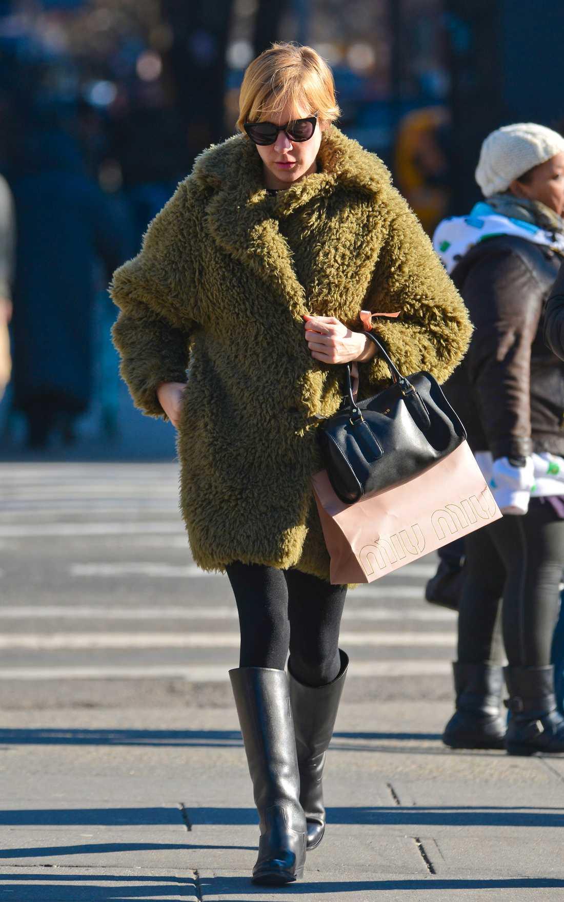 Chloë Sevigny värmer sig i oversizad pälskappa och svarta stövlar.