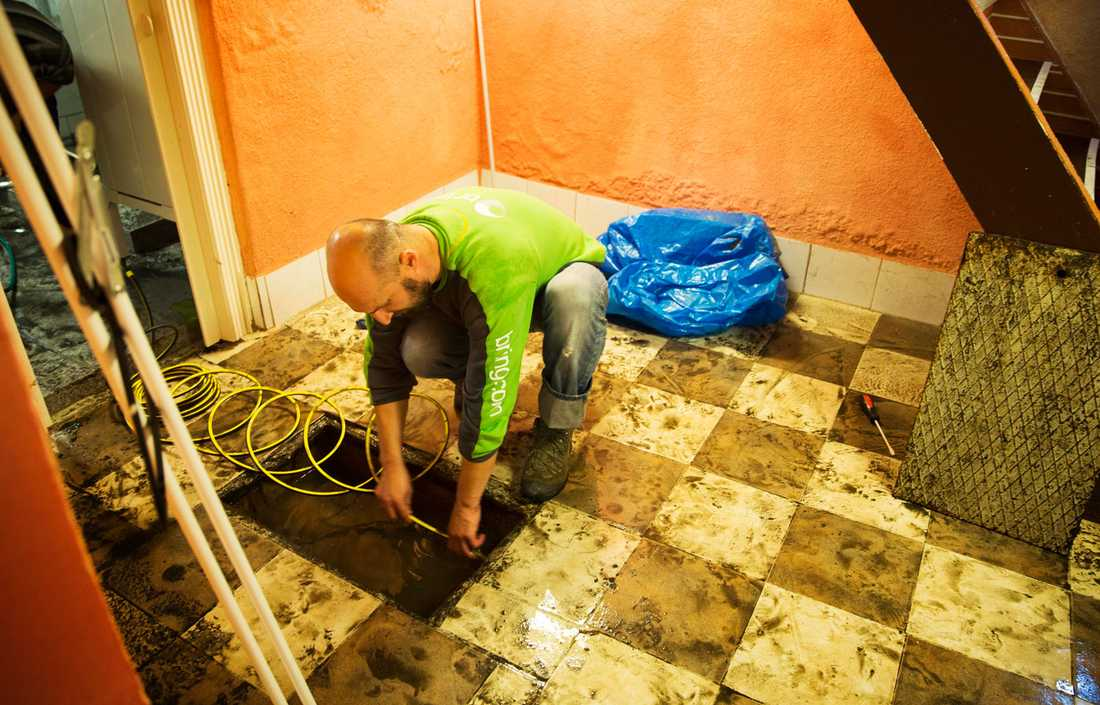 Bahrija Bilalovic hjälper sin vän Damir Masic att pumpa ut vatten från källaren i området Rosengårdsstaden i Malmö.