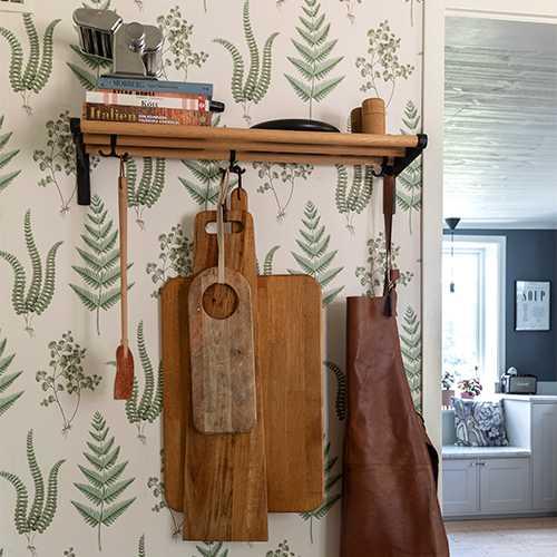 I matrummet mot köket sitter en hylla från Essem design. Flugsmällan med läder kommer från danska Hay och en av skärbrädorna har Benjamin snickrat. Pallen kommer från Ikea.
