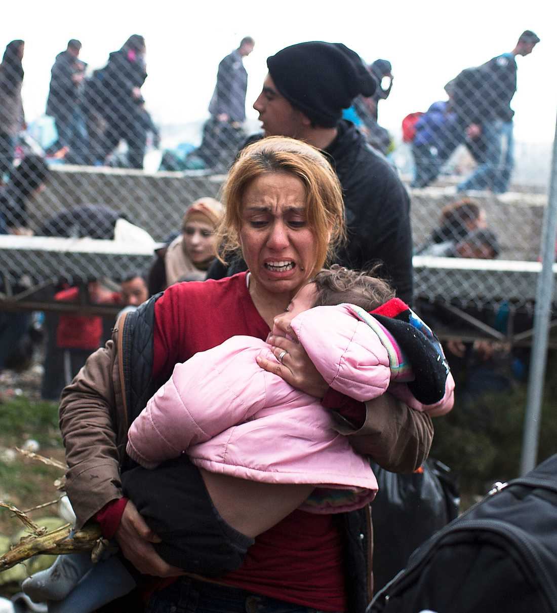 STOPPAS MED GAS En kvinna med ett barn i famnen flyr undan den makedonska polisens tårgasattack vid grekiska gränsen i Idomeni.