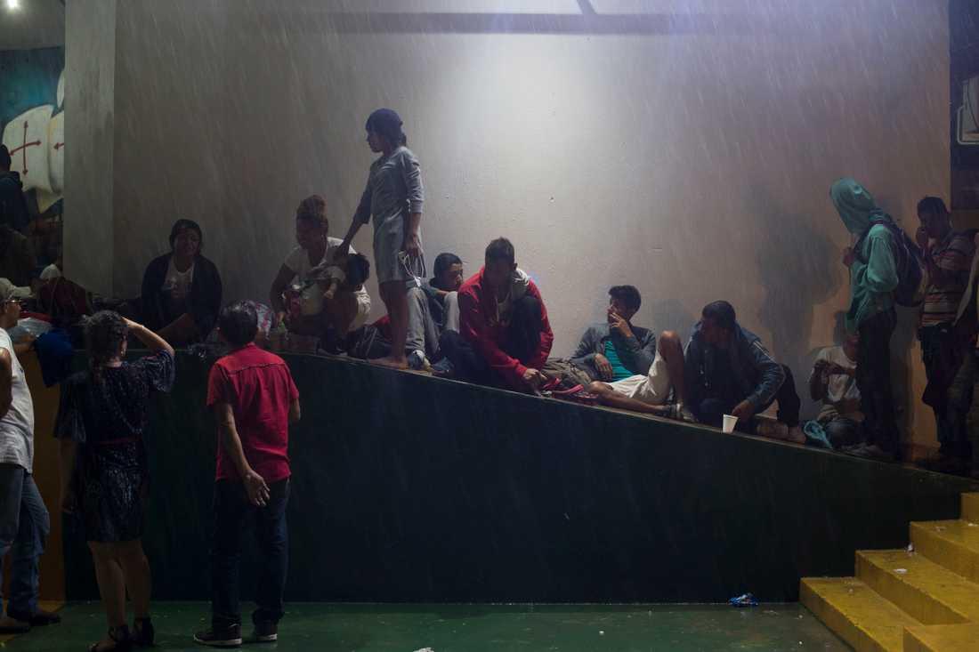 En grupp migranter som anlänt till Tecun Uman, vid gränsen mellan Guatemala och Mexiko, tar skydd från regnet sent på torsdagen.