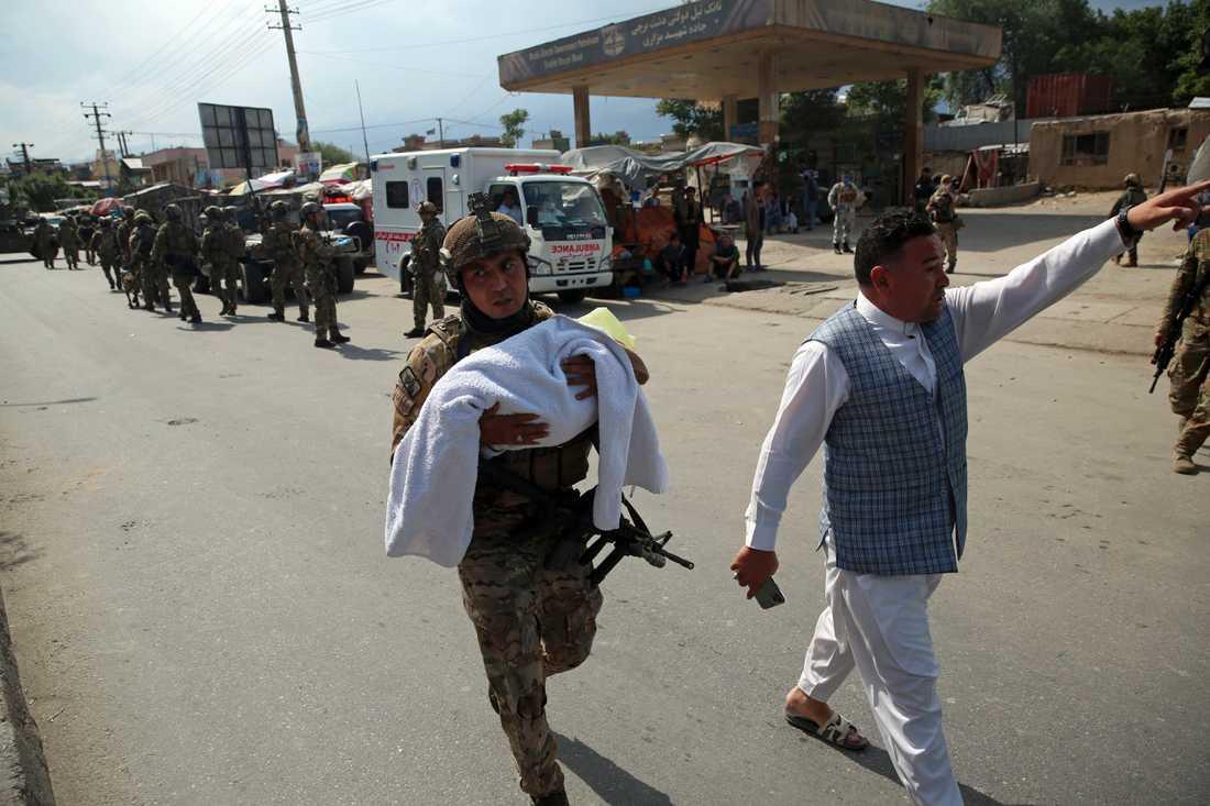 En afghansk soldat bär på ett barn efter att beväpnade män angripit en förlossningsklinik i Kabul i tisdags.