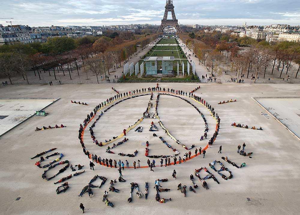 """På fredag är det tänkt att klimattoppmötet i Paris ska vara klart. Det kommer det inte vara, skriver Lena Mellin som bevakar mötet på plats tillsammans med Aftonbladets Anette Holmqvist och Eva Franchell. På bilden ses miljöaktivister bilda Eiffeltorn-fredstecknet och texten """"100% renewable"""", 100 % förnybar."""