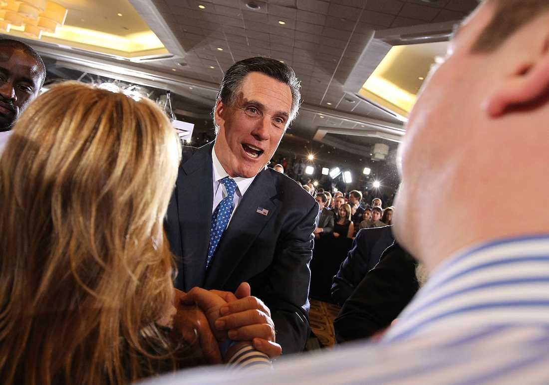 Mitt Romney hälsar på anhängare under valvakan med sin familj i Boston. Romney vann knappt över Santorum och kunde räkna hem delstaterna Ohio, Massachusetts, Vermont, Virginia och Idaho.