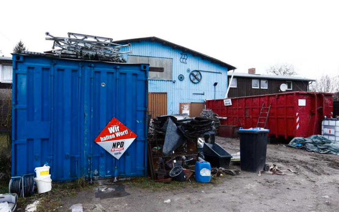 En valposter för högerpartiet NPD sitter uppe på en container i Jamel.