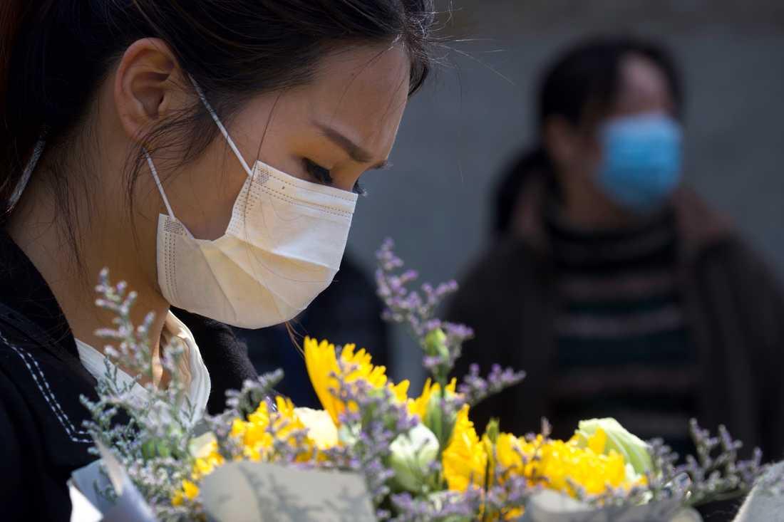 En kvinna med en blombukett i Wuhan i Hubeiprovinsen under den nationella minnestunden på lördagen för alla de som avlidit i sviterna av covid-19.
