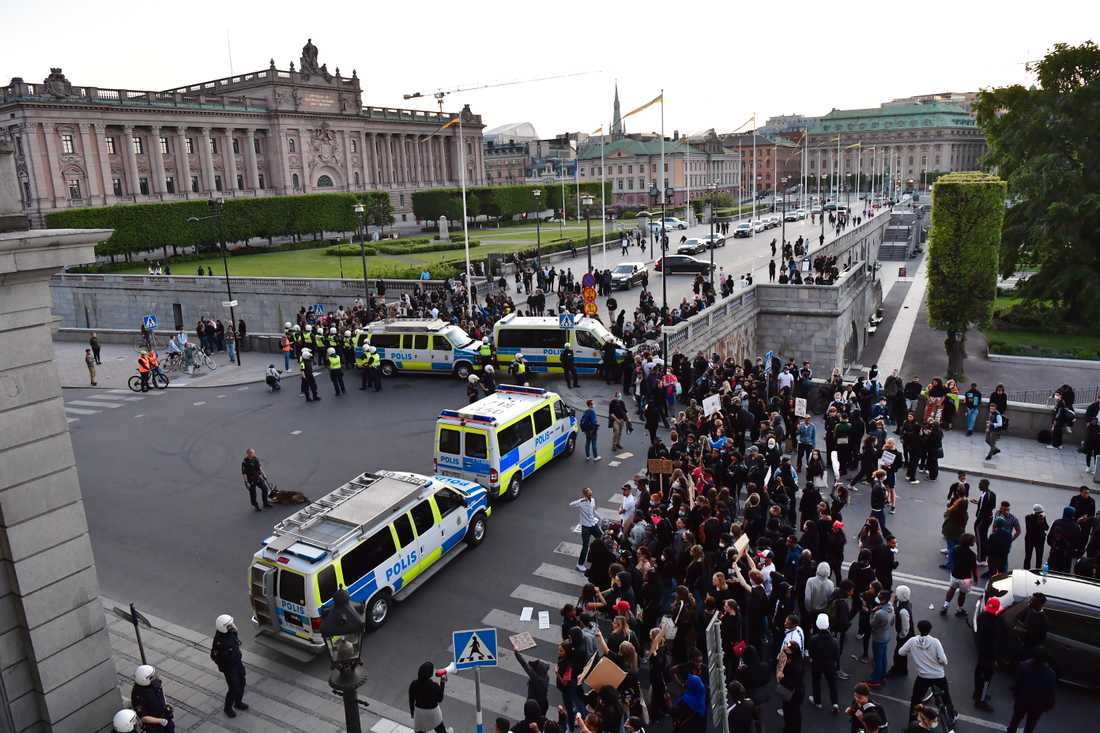 Kravallpoliser stoppar demonstranter nedanför slottet vid Norrbro i Stockholm.