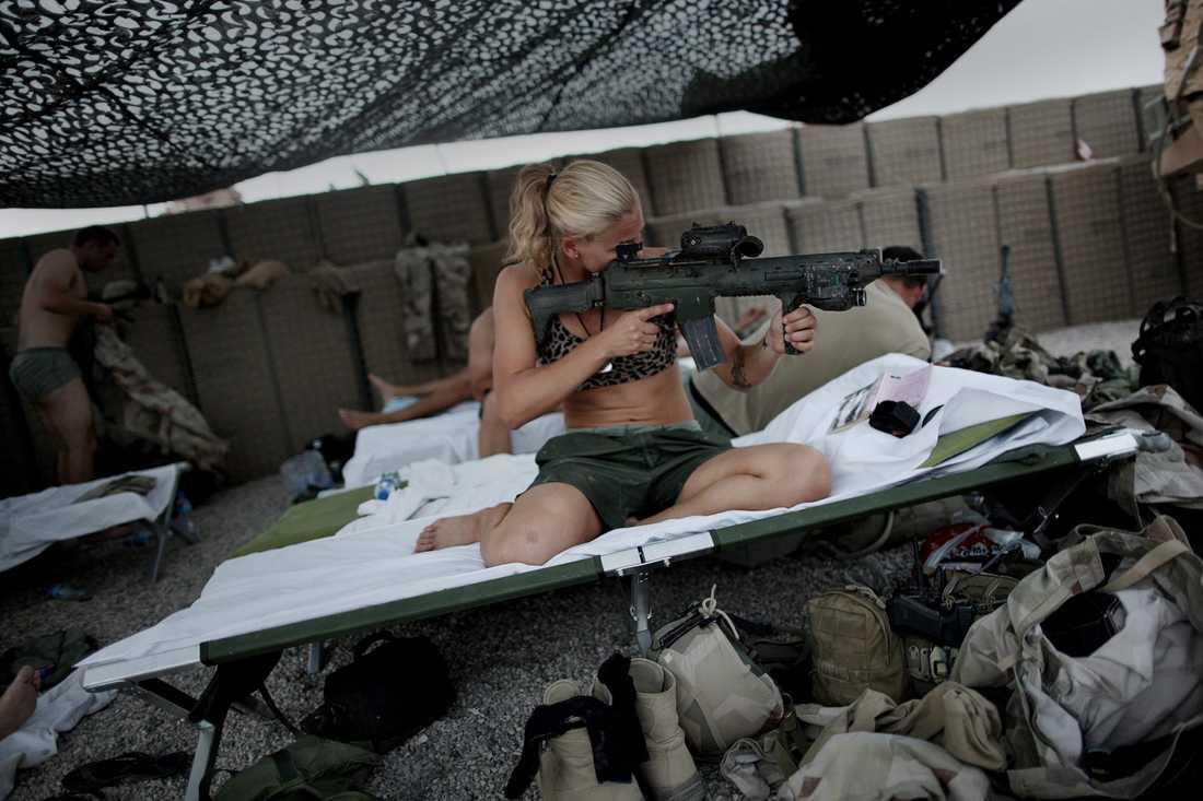 Den svenska soldaten Frida kollar och rengör sina vapen i eftermiddagsvärmen på kullen.