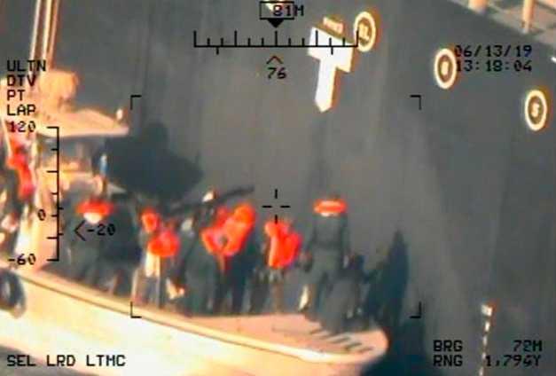Enligt USA är detta iranska revolutionsgardister som försöker ta bort en odetonerad mina från det japanska fartyget som attackerades. Bilden har tillhandahållits av USA:s försvarsdepartement.