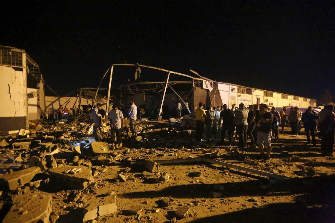 Räddningsarbetare gräver fram döda efter luftangreppet mot migrantlägret Tajoura.