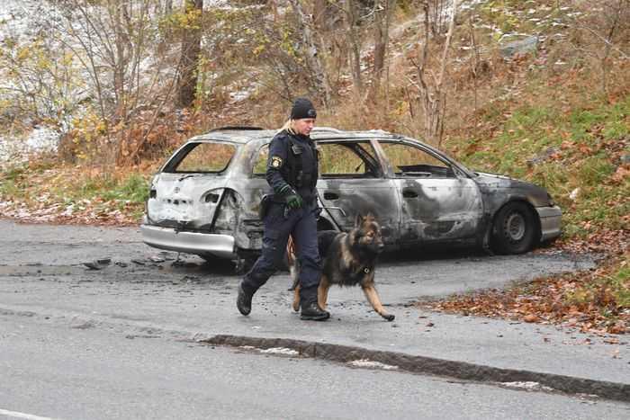 Polis söker spår vid den utbrända flyktbilen.
