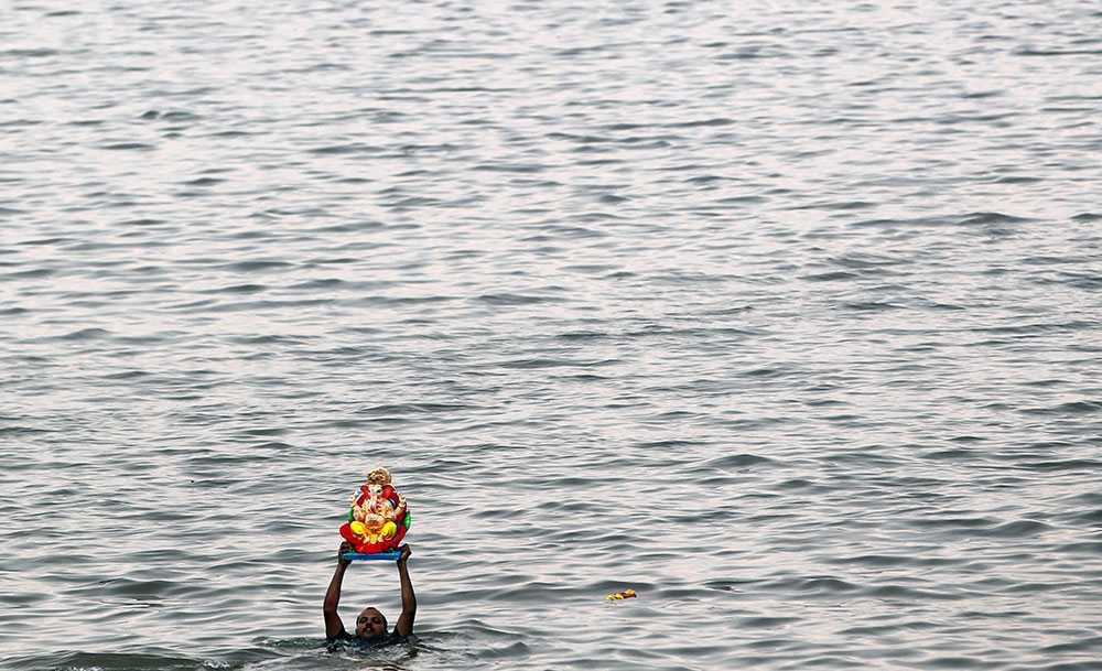 En indisk man simmar med en staty av den hinduiska guden Ganesha i Arabiska havet. En årlig festival i staden Mumbai pågår just nu för att hylla guden.