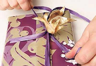 5. Lägg sidenbanden ovanpå varandra och knyt om med basten på mitten så att rosetter bildas. Knyt in ytterligare några småbitar dekorationsbast.