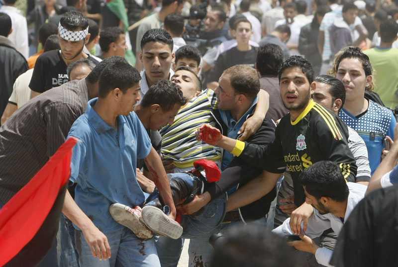 """En ung palestinier tas omhand av sina vänner. Han skadades vid Gaza i samband med oroligheter under katastrofdagen """"Nakba"""". Enligt israeliska tv-kanalen Channel 2 TV har minst fyra personer dödats när israeliska armén öppnade eld. Läkarkällor säger att minst 45 personer skadades när israeliska armén öppnade eld."""
