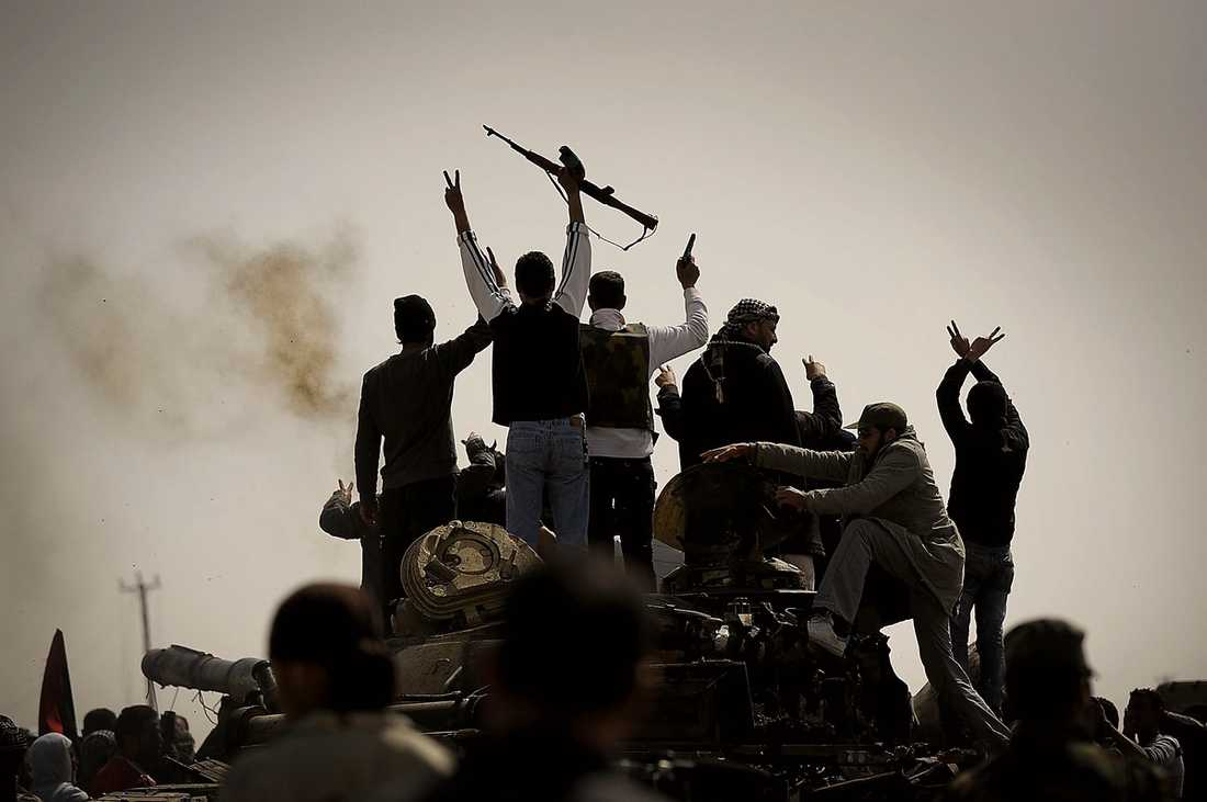 Männen i Ajdabiya bär vapen och skjuter i luften för att fira segern.