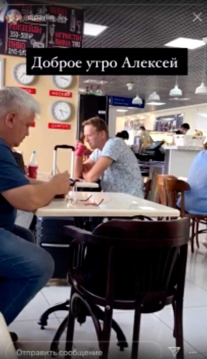 """Bild tagen ur medpassageraren Pavel Lebedevs film, där Aleksej Navalnyj dricker te på flygplatsen i Tomsk. """"God morgon, Aleksej"""", står det skrivet i bilden."""