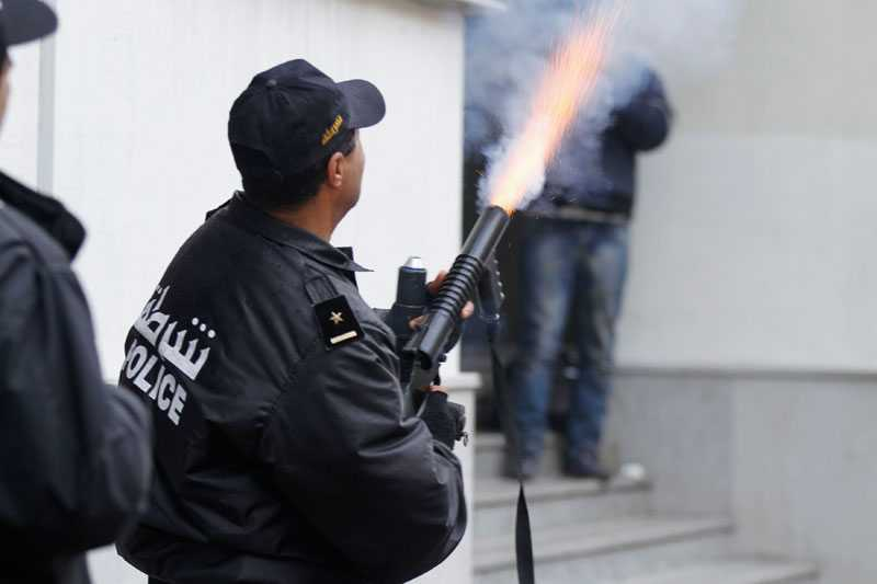 En polis fyrar av tårgås mot demonstranter i Tunis.