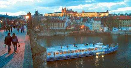 Skymningsljuset ger ett romantiskt skimmer över Prag. Från vattnet får man en annorlunda vy av Karlsbron och borgen.