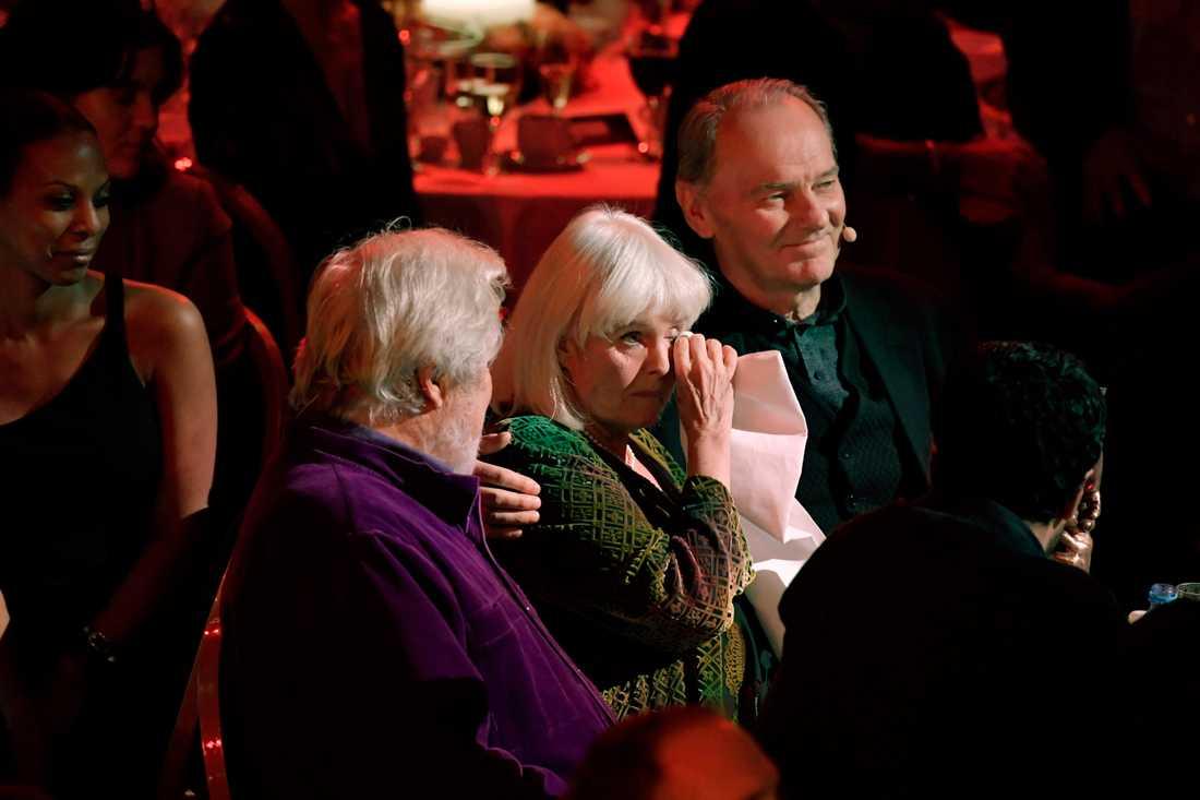 En märkbart tagen Anita lyssnade på Mikael Wiehes sång mellan Sven Wollter och Björn Granath.