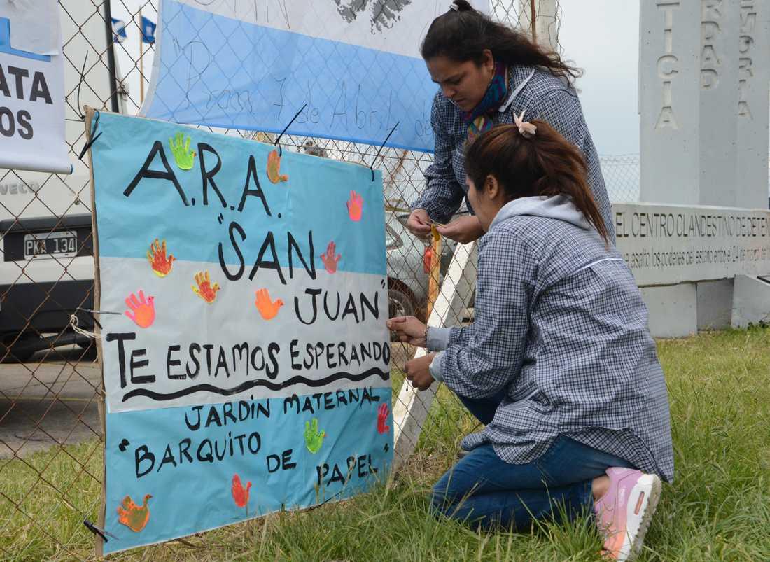 """Lärare från en skola hänger upp en skylt i Argentinas färger med texten: """"ARA San Juan, vi väntar på dig""""."""