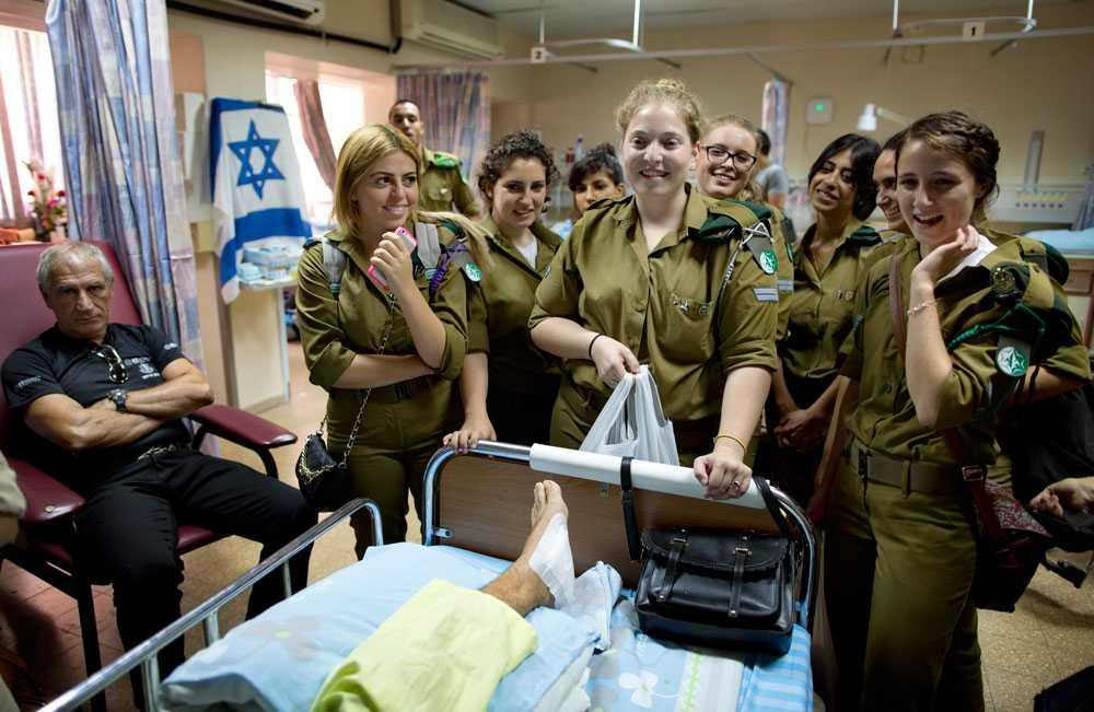 Israelisk militär hälsar på hos en soldat som har skadats under konflikten. Över 50 israeler har dött under den senaste offensiven, de flesta av dem soldater.