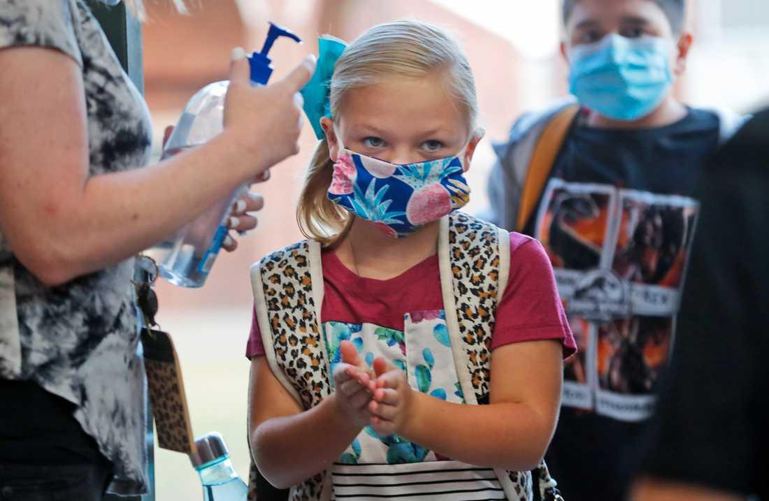 Elever på en grundskola i Godley, Texas, desinfekterar sina händer inför skoldagen. Arkivbild.