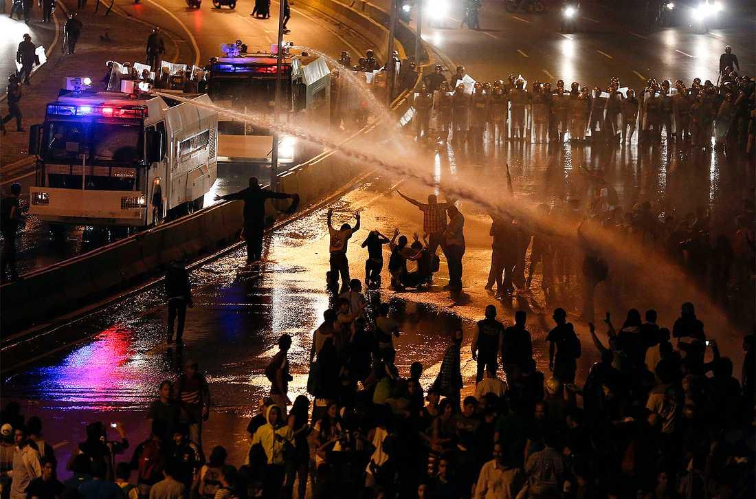 Kravallpolis skjuter med vattenkanon mot demonstranterna.