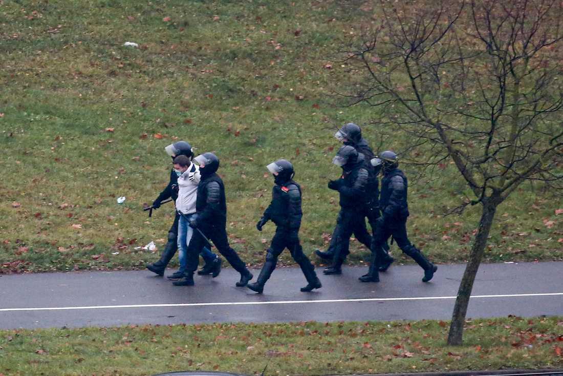 En man förs bort av kravallpoliser vid demonstrationerna i Minsk.