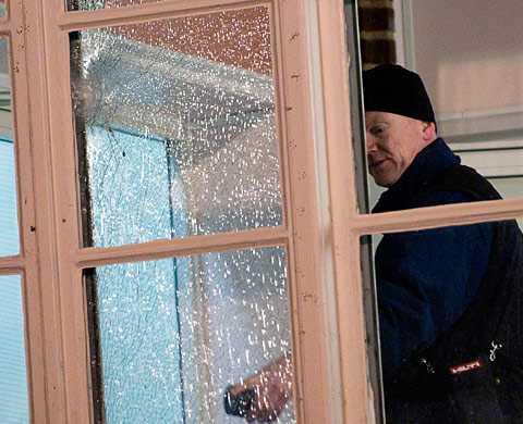 En polis undersöker skadorna på polishuset i Malmö som besköts i mars 2010.