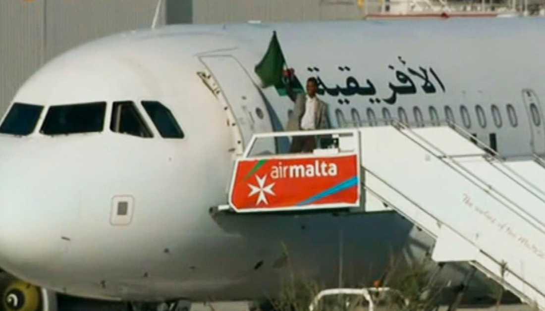 En av kaparna viftar med en flagga utanför flygplanet på Malta i december 2016. Arkivbild.