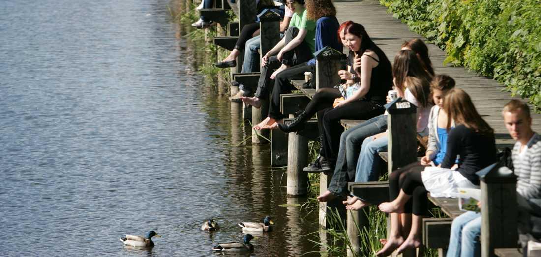 Snart men inte än. Studenter i Uppsala njuter av vårvärmen vid Fyrisån. Våren är på gång men denna helg blir det blåsigt och blött.
