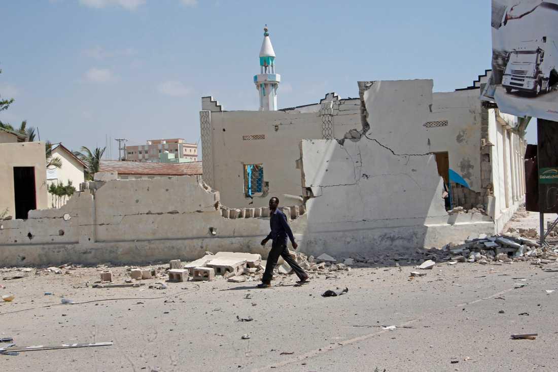 En man går förbi förstörda byggnader efter en explosion i Mogadishu. Somalias huvudstad utsätts ofta för dåd av islamistgruppen al-Shabaab. Arkivbild.
