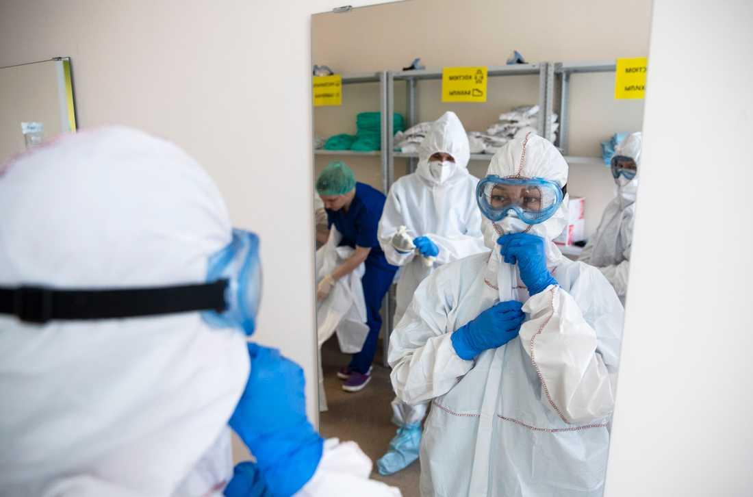 Vårdpersonal sätter på sig skyddsutrustning inför ett pass på intensivvårdsavdelningen på Vinogradov-sjukhuset i Moskva. Bilden är från den 21 april.