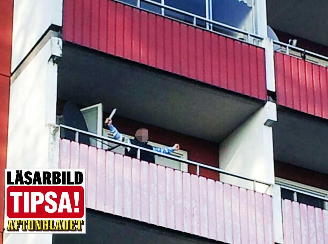 Mannen stod och viftade med macheten på balkongen.