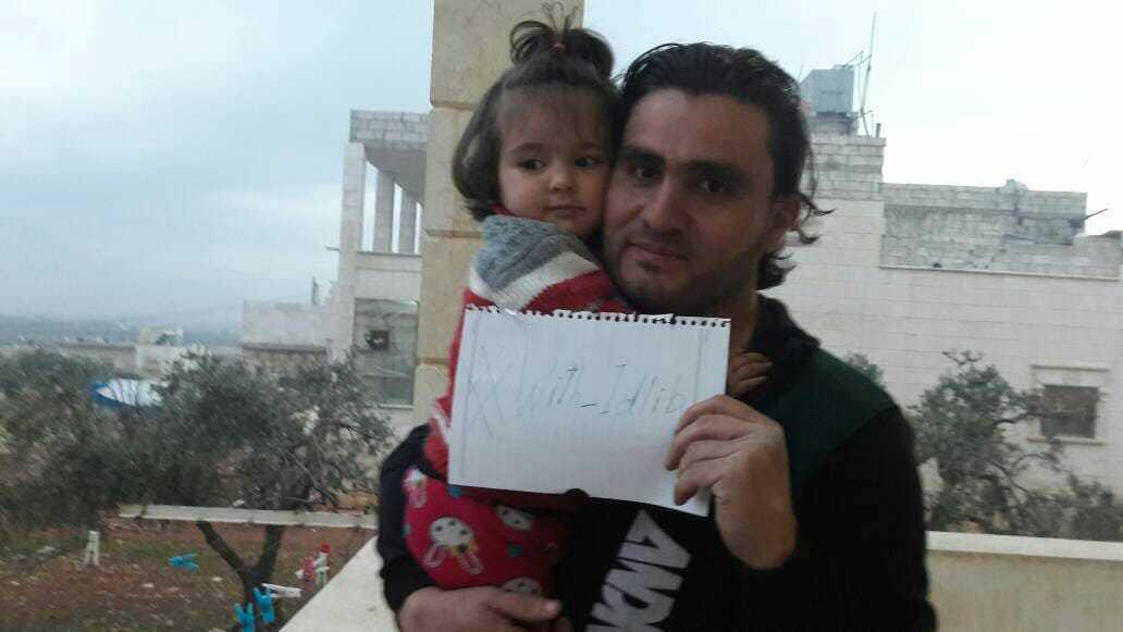 Den syriske läraren och aktivisten Abdulkafi Alhamdo tillsammans med dottern Lamar 2018. I handen håller han en lapp som uppmanar till sympati med Idlib. Arkivbild.