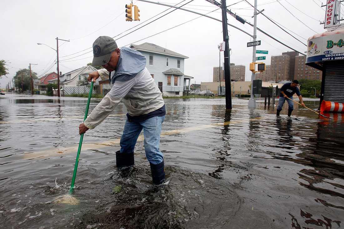 Queens, New York: En man använder en kvast för att rensa galler till en brunn.