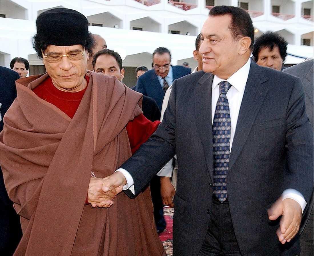 Skakar hand med Egyptens avsatte president Hosni Mubarak.
