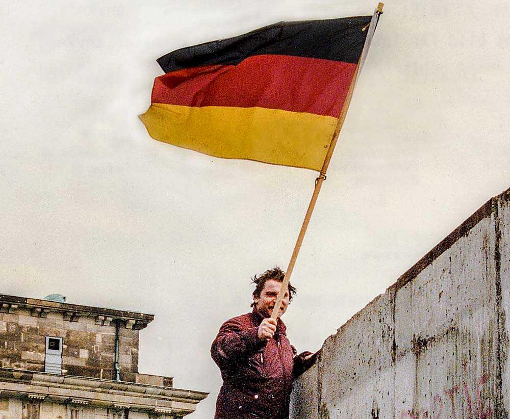 En västtysk Berlinbo  tittar över på östsidan  i samband med murens fall i november 1989.