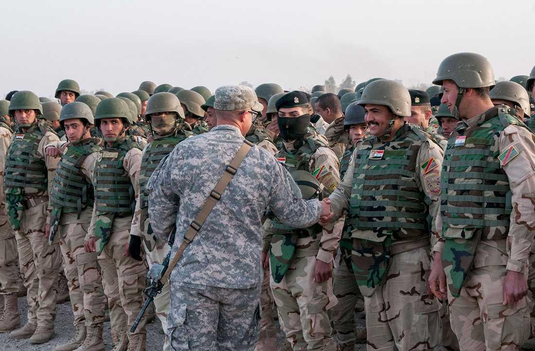 En amerikansk officer hälsar på irakiska soldater.