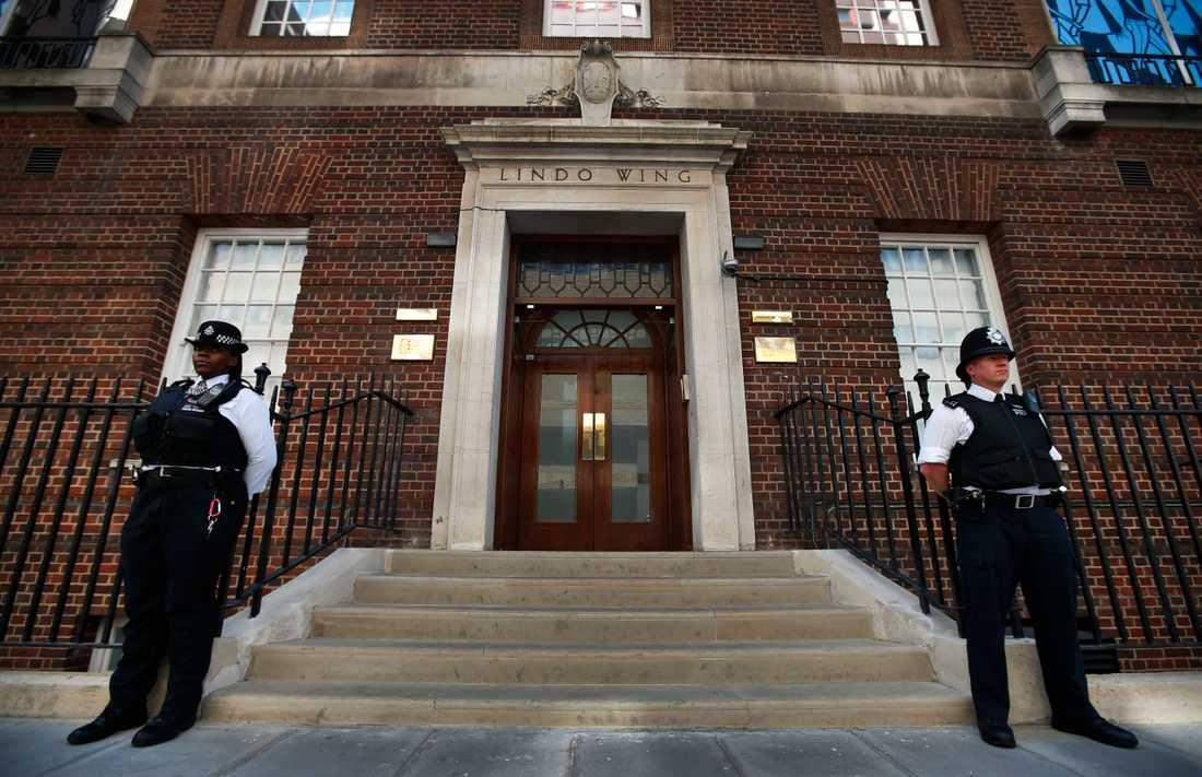 Här vaktar poliserna dörren till sjukhuset där Kate Middleton födde en ny kunglig bebis. Utanför sjukhuset väntade massor med media som slogs om de bästa platserna.