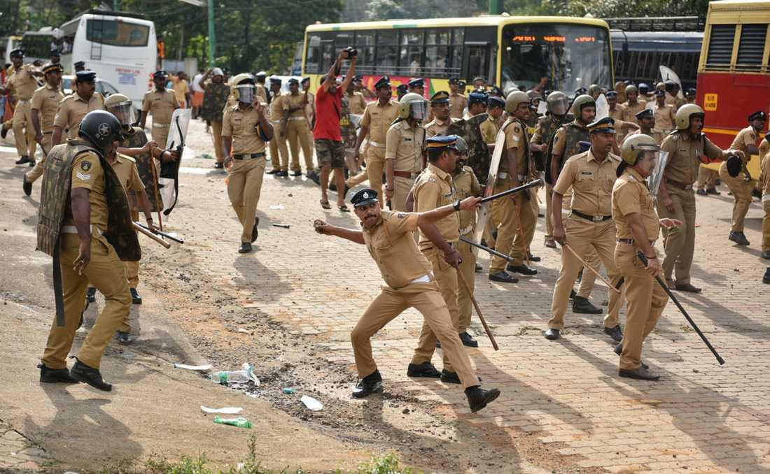En polis kastar tillbaka en sten i samband med de våldsamma protester som försökte stoppa kvinnor som försökte besöka Sabarimalatemplet i mitten av oktober, efter att ett förbud för kvinnor upphävts av Högsta domstolen. Arkivbild.