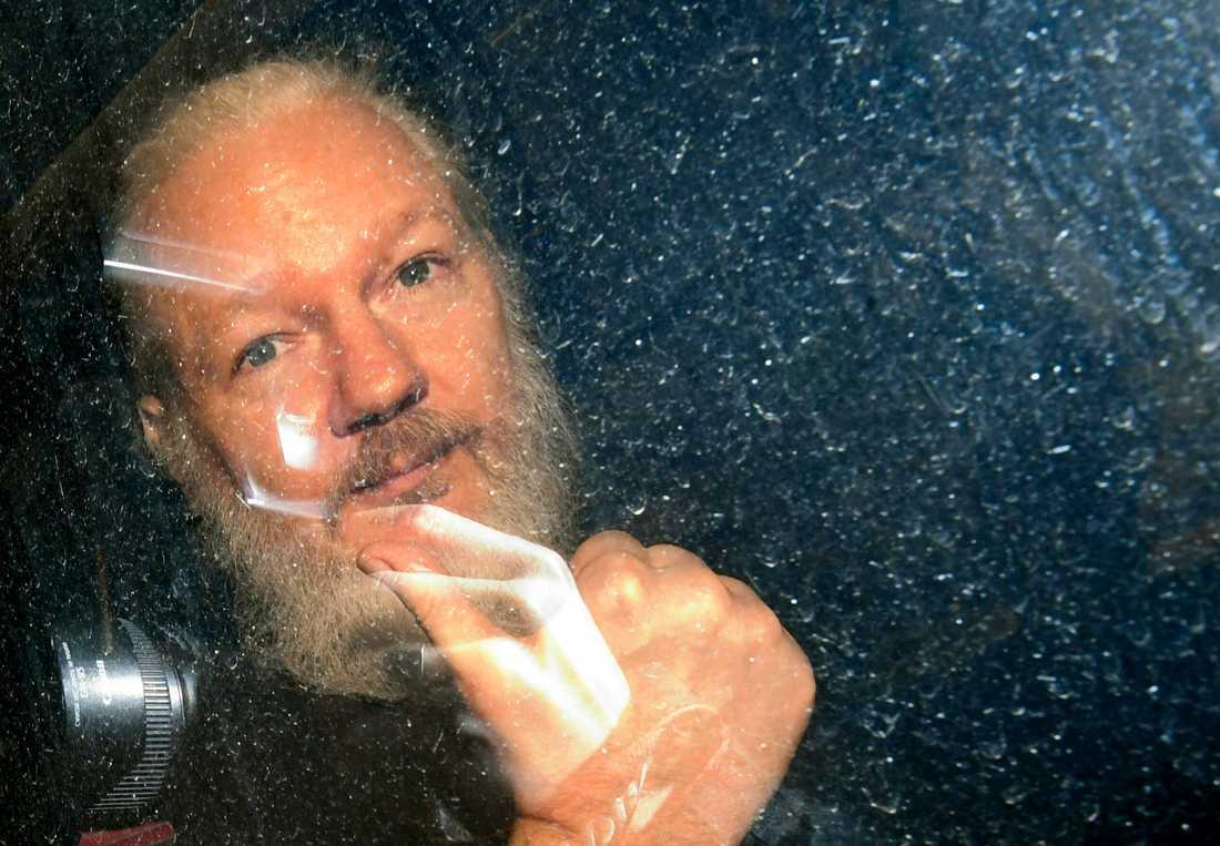 Assange förs iväg av polis.
