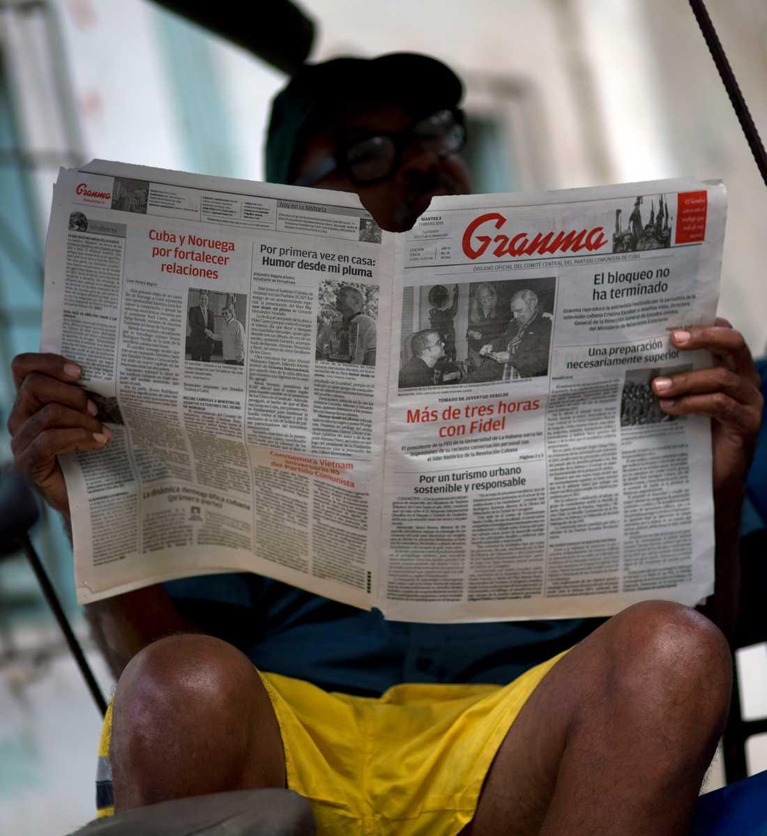 En man läser ett exemplar av det kubanska kommunistpartiets officiella organ Granma, ett av de medier som stängts av på Twitter. Arkivbild.