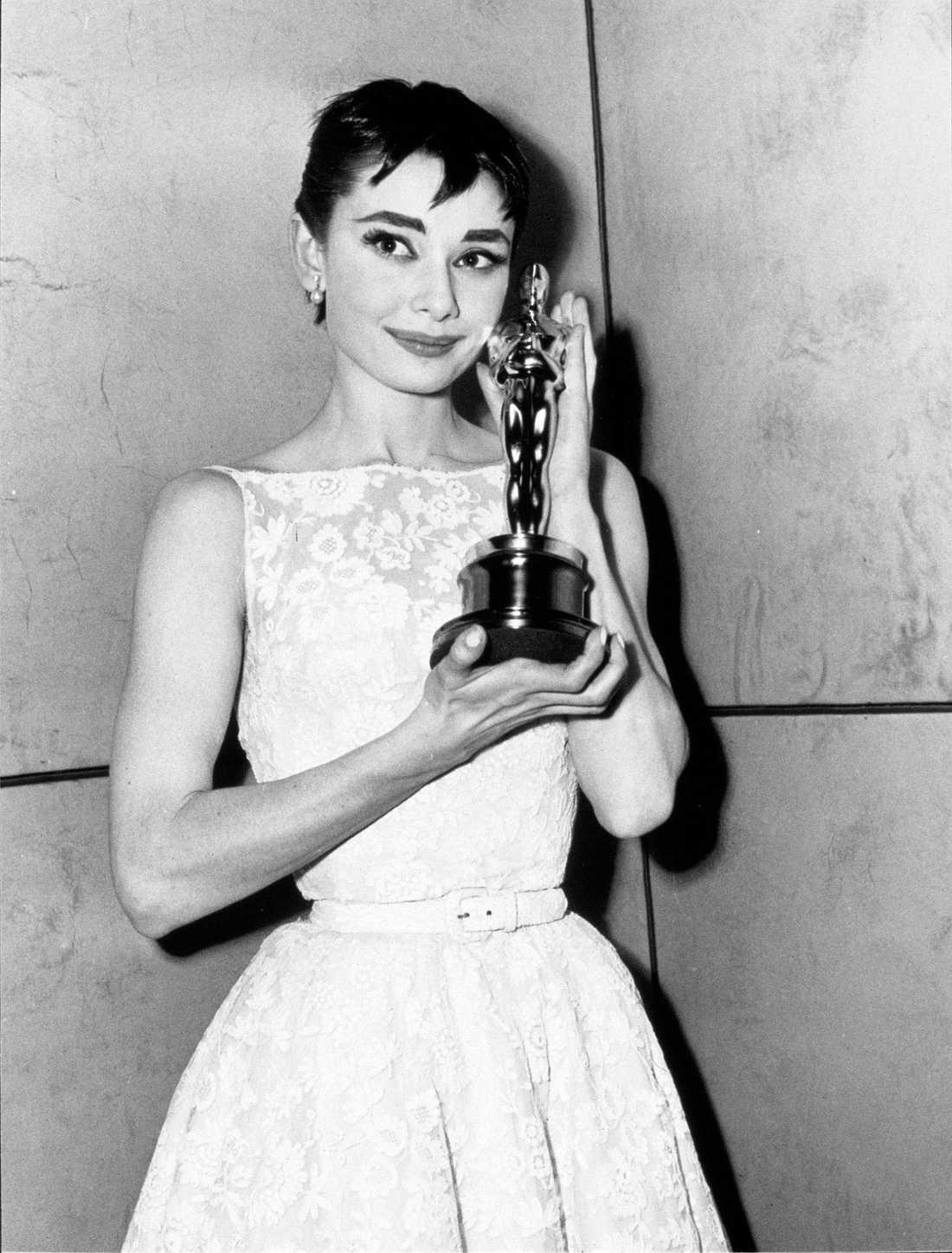 """Audrey Hepburn 1954 """"Inte nog med att världens mest kända och älskade skådespelerskor bär en vit, krispig och delikat klänning från Givenchy. Hon vinner dessutom en Oscar och tar emot statyetten med en kort svincool pixiefrisyr. Därmed har denna look för alltid blivit ansedd som """"the best of all times"""". Jag kan bara hålla med."""""""