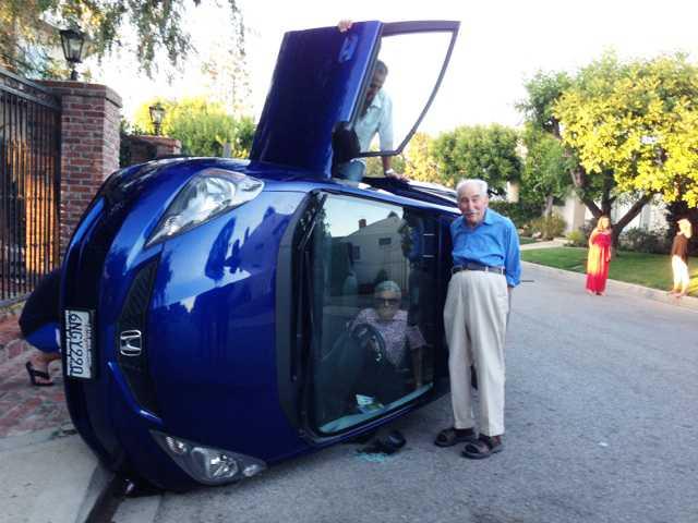 När ett äldre par körde omkull med bilen lät de sig fotograferas – trots att kvinnan fortfarande satt fast. Nu sprids bilderna över världen.