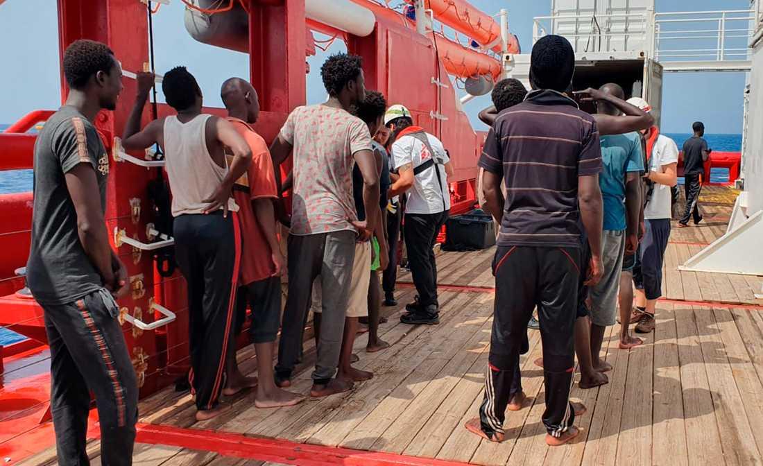 Räddade migranter köar för att bli registrerade på fartyget Ocean Viking.
